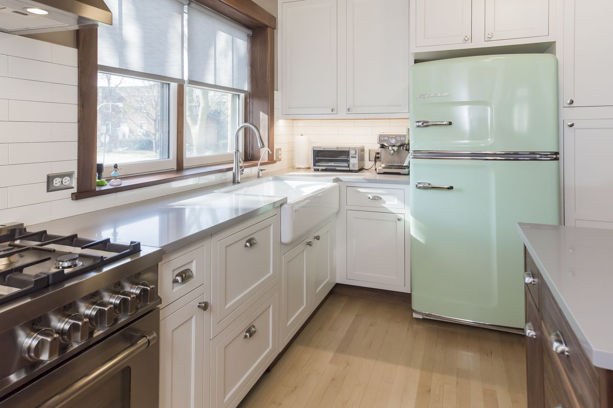 A renovated kitchen with white cabinets, dark wood frame around windows, a mint 50s-style refrigerator, new appliances and shiplap.