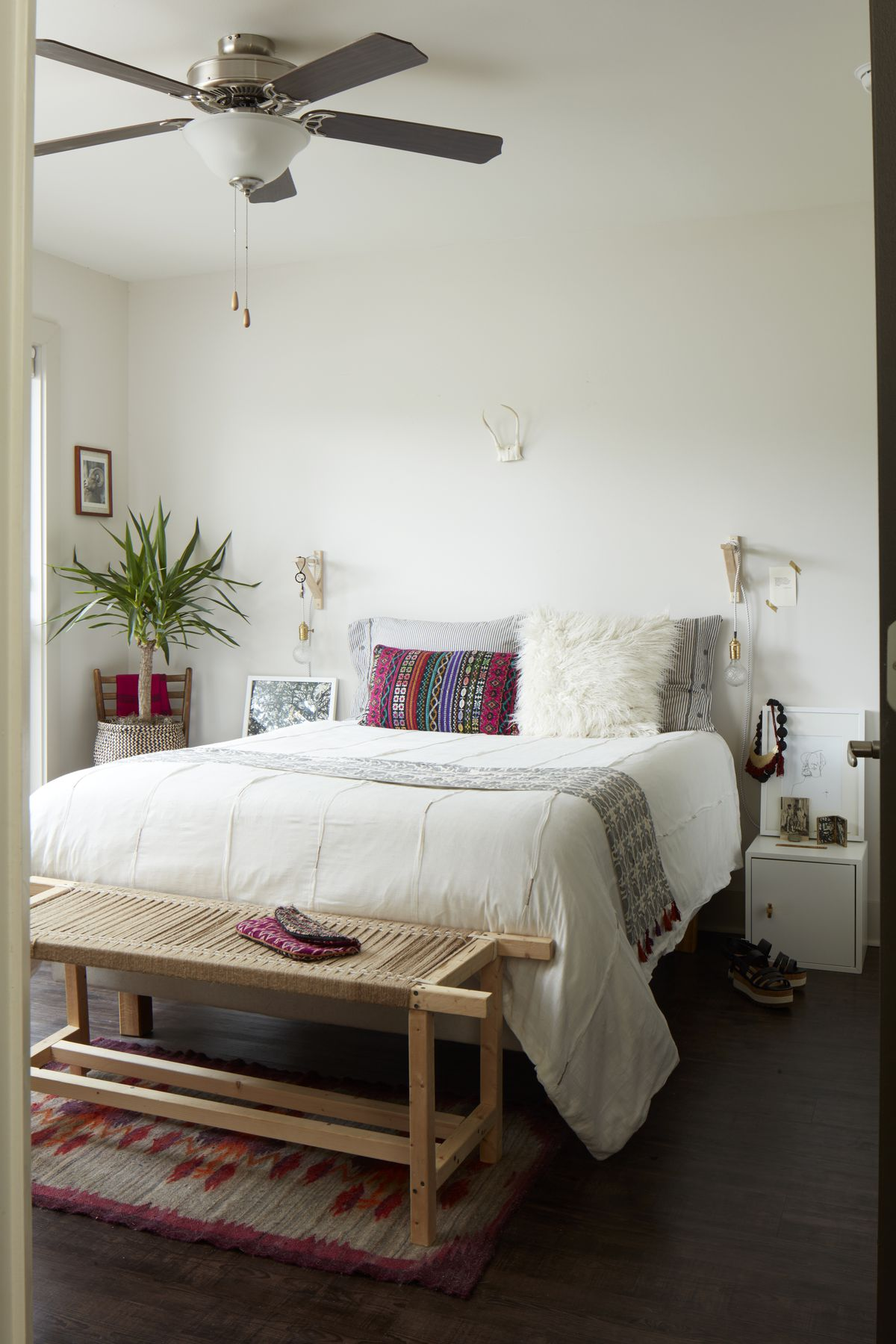 A white bedroom has a natural wood bench in front of it. Shorthouse made the bench with a friend.
