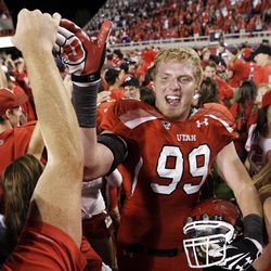 Utah fans storm the field and high five Utah Utes defensive end Joe Kruger (99) after the Utes beat BYU in Salt Lake City on Saturday.