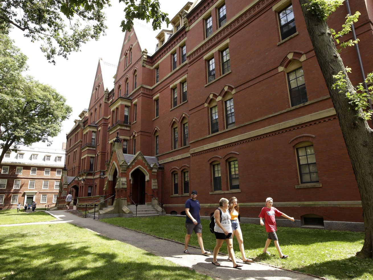 People walk along a sidewalk on the campus of Harvard University, in Cambridge, Mass.