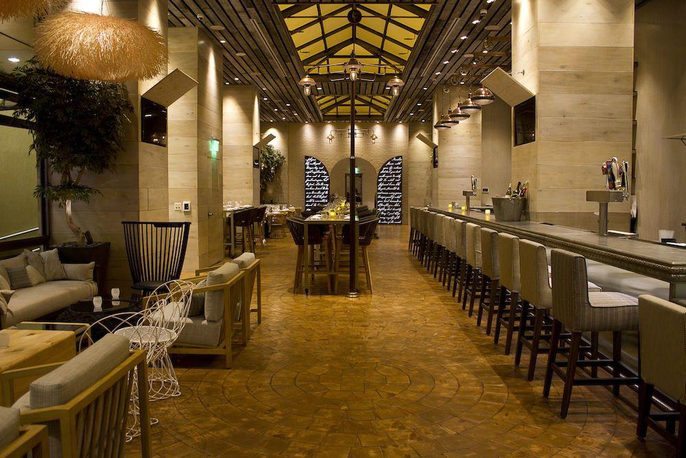 A warmly lit bar area with wood floors and an atrium