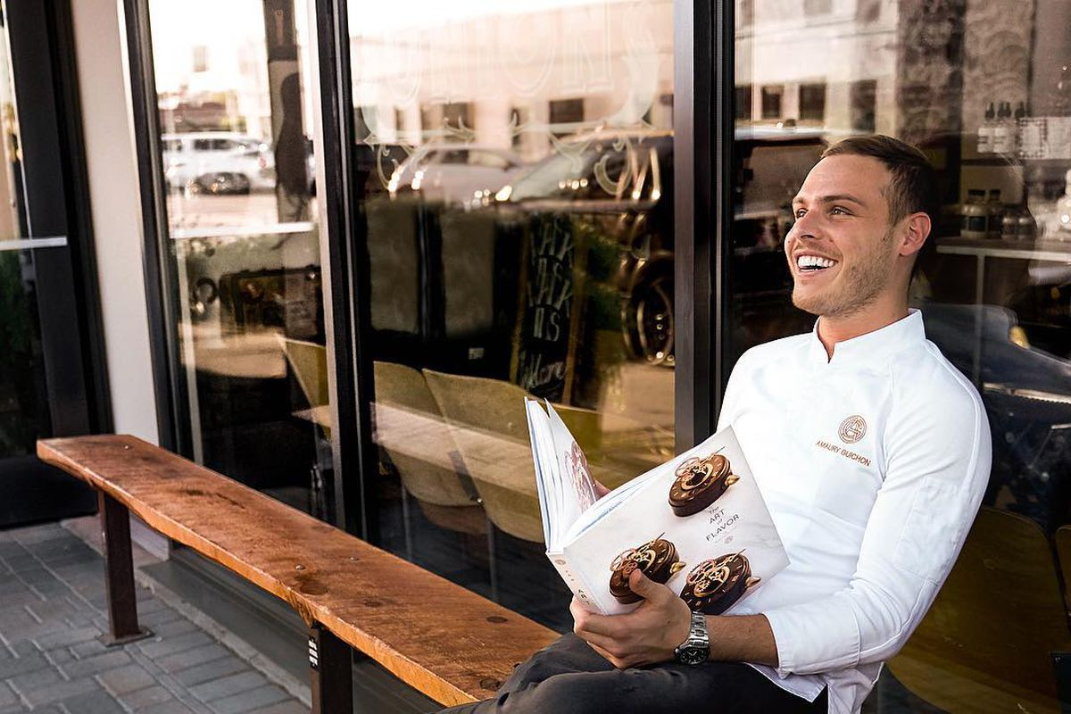 A man in a white jacket sits on a wooden bench holding a cookbook