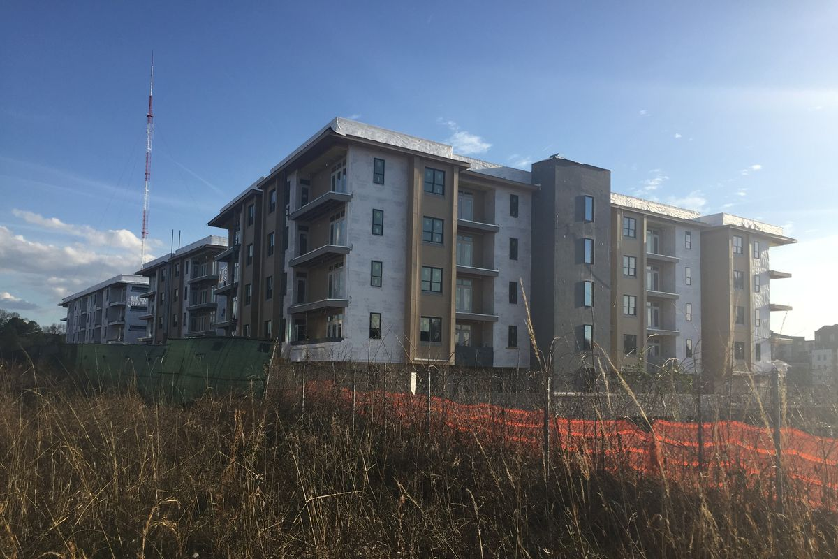 A five-story modern apartment building, rising above tall grass along the Beltline.
