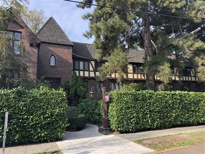 Behind a boxwood hedge is a building with a square, brick turret and half-timbering.