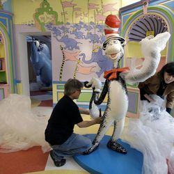 """In this May 4, 2017, photo John Simpson, left, project director of exhibitions for The Amazing World of Dr. Seuss Museum, and his wife Kay Simpson, right, president of Springfield Museums, unwrap a statue of the """"Cat in the Hat,"""" at the museum, in Springfield, Mass. The museum devoted to Dr. Seuss, which opened on June 3 in his hometown, features interactive exhibits, a collection of personal belongings and explains how the childhood experiences of the man, whose real name is Theodor Geisel, shaped his work."""