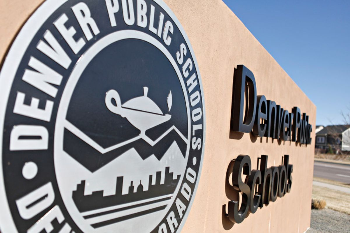 A concrete outdoor sign for Denver Public Schools, showing the district's logo of an Aladdin-style lamp atop the profile of mountains.