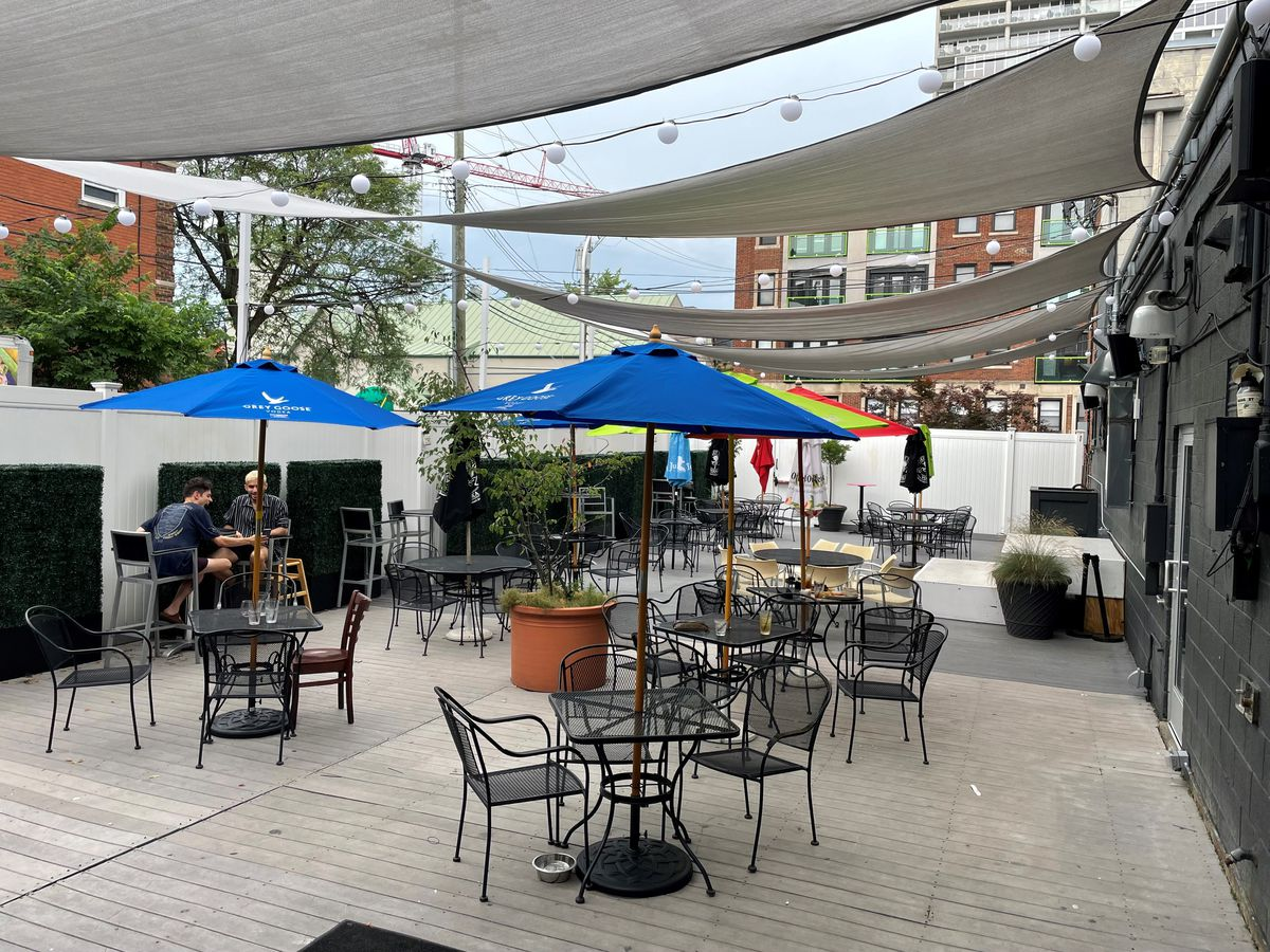 A patio with cloth shade covers overhead and blue umbrellas and wrought iron chairs