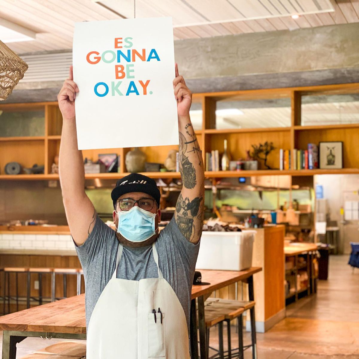 """A man in a facial mask and black hat and apron holding up a sign that reads: """"Es Gonna Be Okay"""" in a restaurant"""