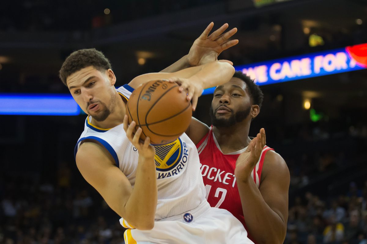 The Warriors' Klay Thompson hauls in a rebound over the Rockets' Jeremy Tyler