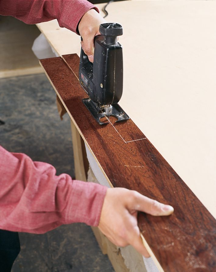 Man Rips Floating Wood Plank To Width Using Jigsaw To Fit Underneath Casing