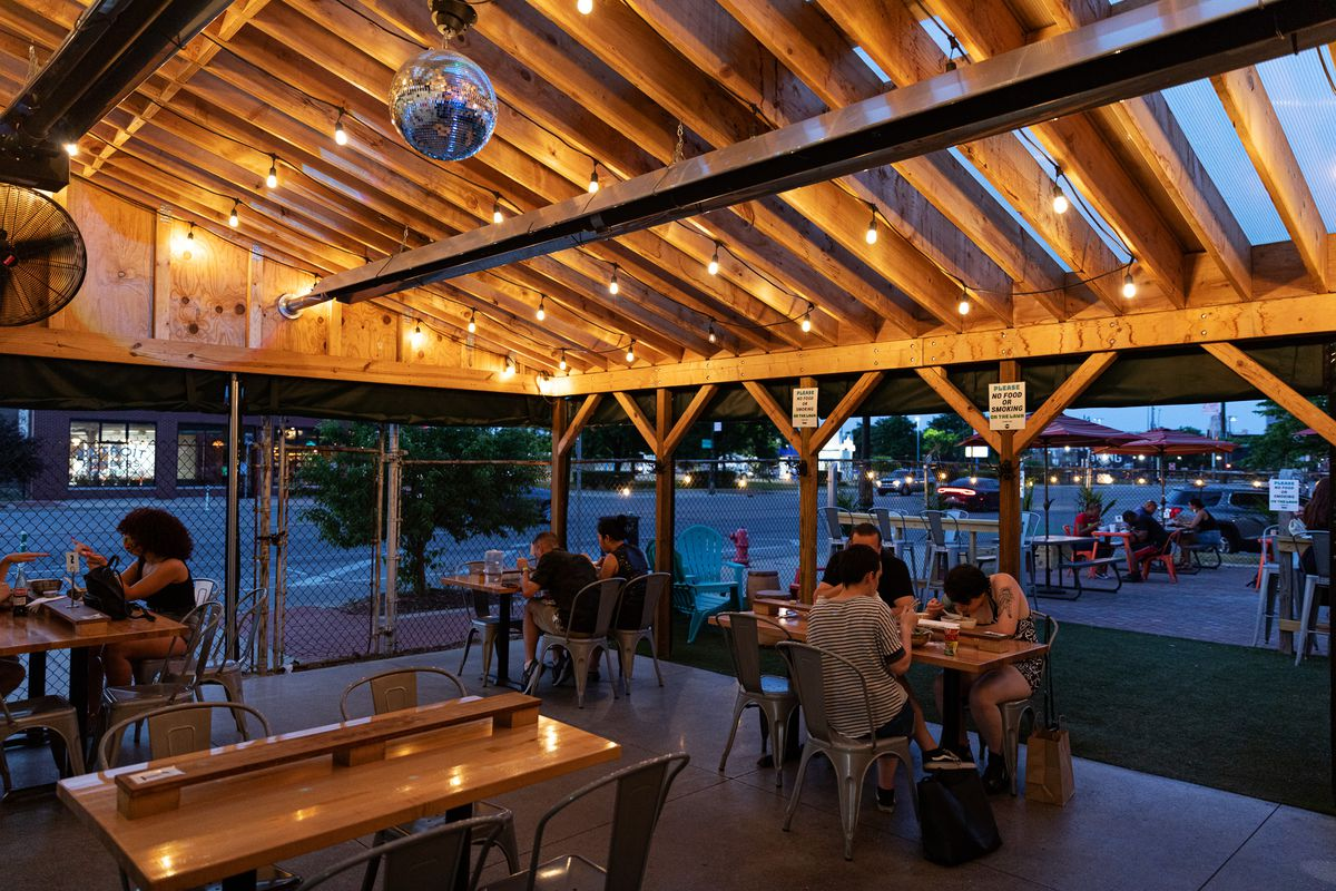 Ima customers sit under a pergola with a disco ball at twilight. Some wear masks while seated while others who've received their food have removed their masks to eat.