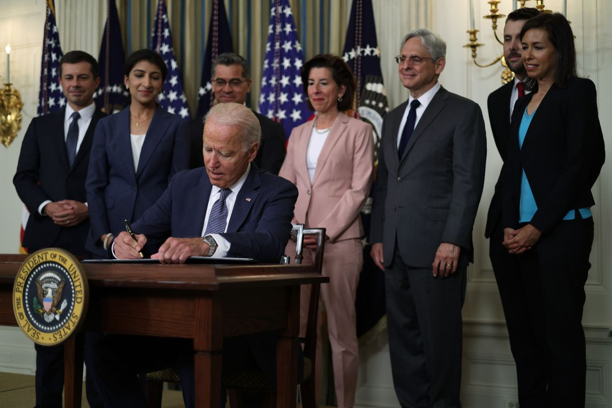 President Biden is seated as he signs the Executive Order on Promoting Competition in the American Economy. He is surrounded by a group of men and women looking on as he signs.