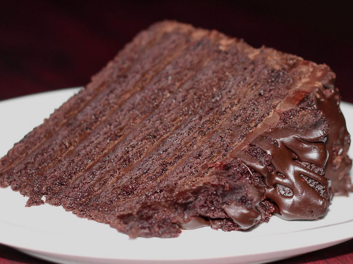 A slice of layered chocolate cake laying on a plate on a black background