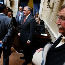 Elder Ronald A. Rasband, a member of the Quorum of the Twelve Apostles of The Church of Jesus Christ of Latter-day Saints, center, chats with senators prior to giving the opening prayer in the Senate on the first day of the Legislature at the Capitol in Salt Lake City on Monday, Jan. 25, 2016.