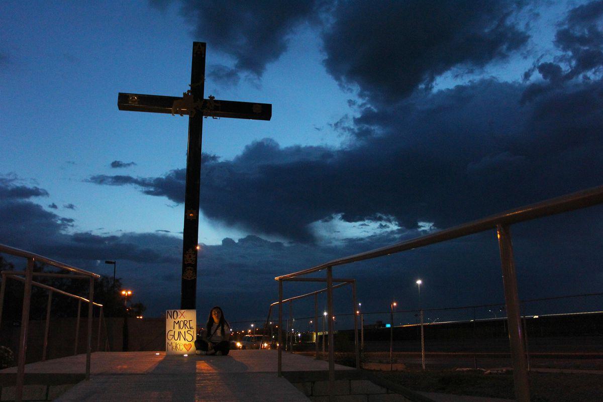 A cross memorial seen against a night sky.