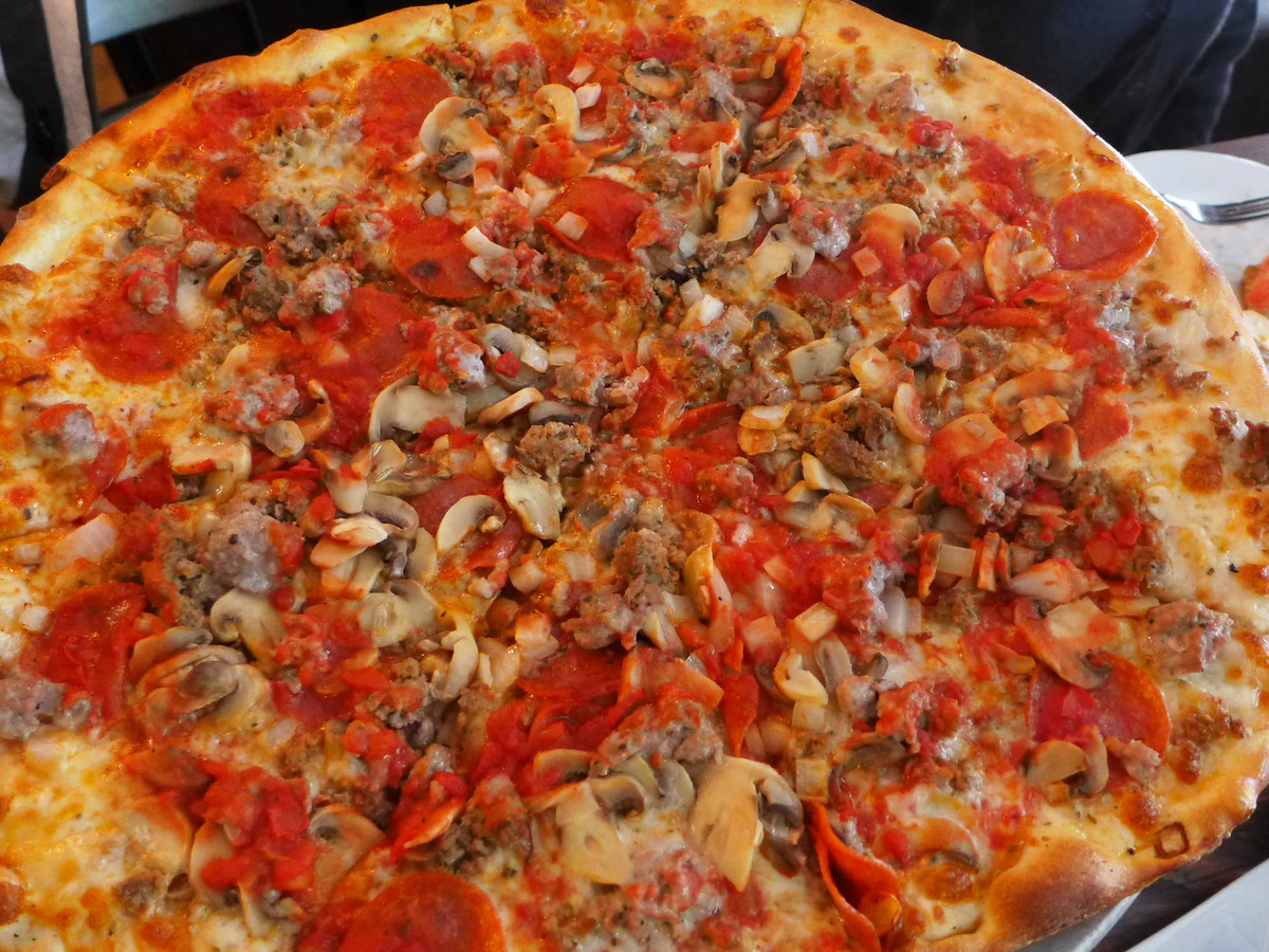A round pizza pie with peppers and mushrooms that's been cut into slices