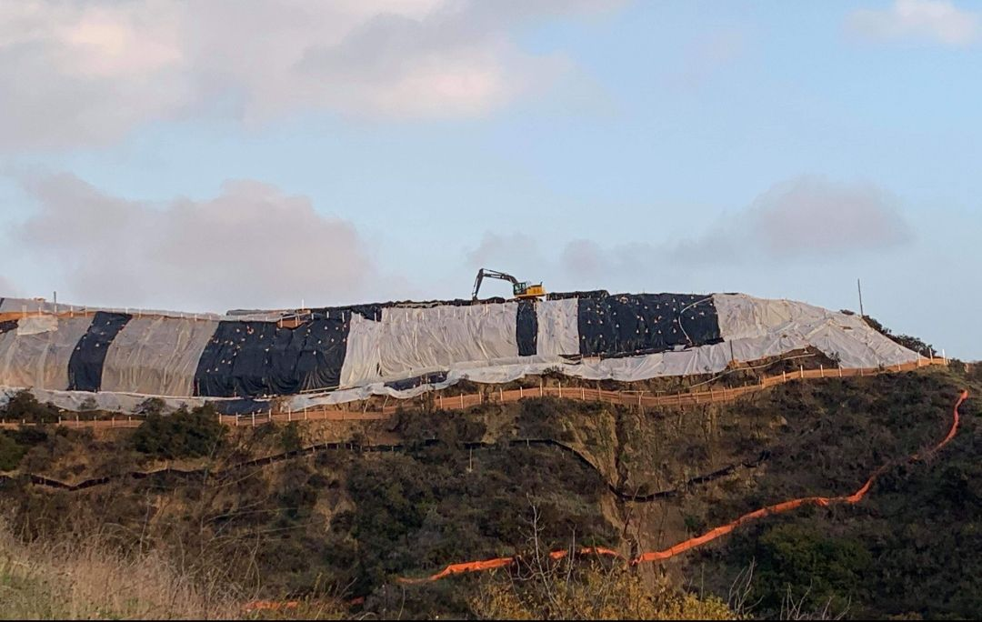 A photo of a flat-topped hillside with plastic tarps on its sides and a large excavator atop the hillside.