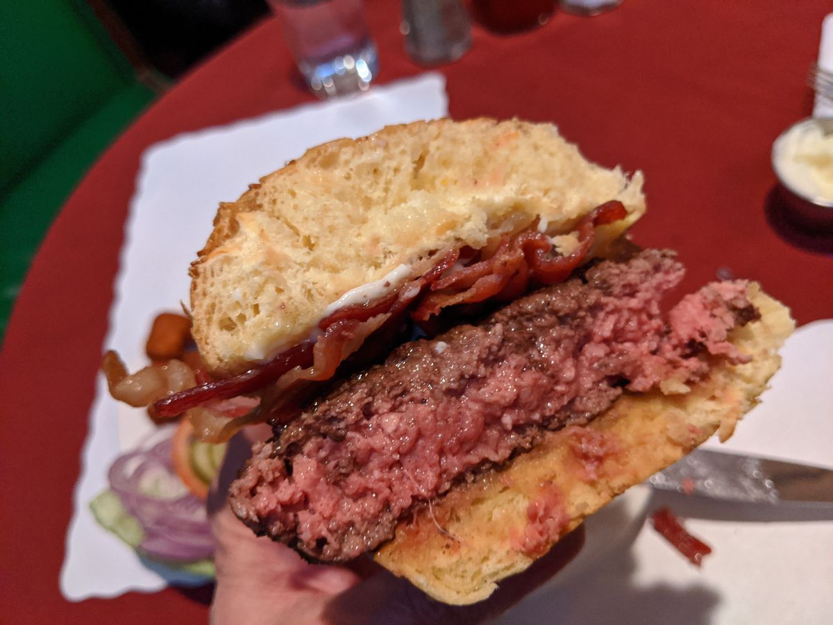 A burger cut in half to reveal a bright red interior.