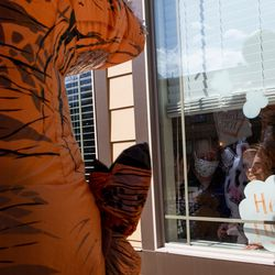 Garrett Duncan, a volunteer with Bristol Hospice Utah, waves to a resident of Spring Gardens Assisted Living in Holladay while wearing a T-rex inflatable costume on Saturday, April 18, 2020.