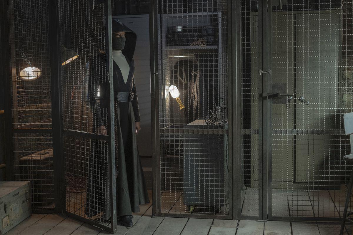 Angela enters a secret storage space.