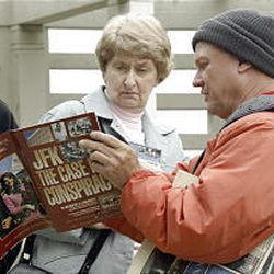 Nancy Sumrall from Cedar Park, Texas, listens as vendor Fred Browning shows her a publication on theories about the John F. Kennedy assassination.