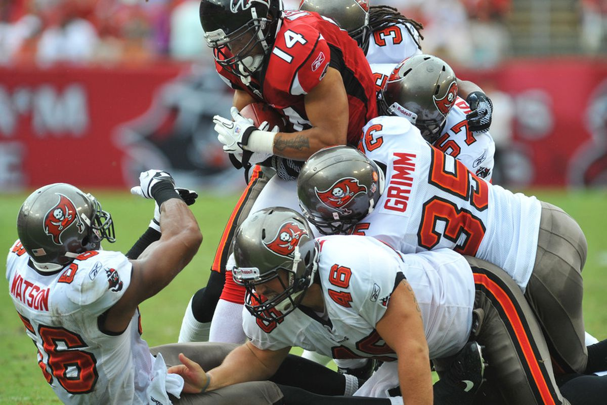 TAMPA, FL - SEPTEMBER 25:  Defenders of the Tampa Bay Buccaneers stop wide receiver Eric Weems #14 of the Atlanta Falcons  on a punt return September 25, 2011 at Raymond James Stadium in Tampa, Florida. (Photo by Al Messerschmidt/Getty Images)