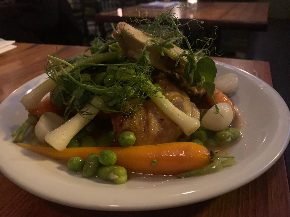 A plate of spatchcocked poussin, with carrots, peas, turnips, and spring onions in a Madeira jus, one of the best dishes in London restaurants