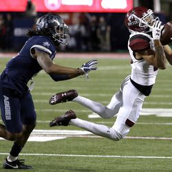 New Mexico State wide receiver Johnathan Boone (13) makes a catch for a first down in front of Utah State cornerback Wesley Bailey in the second half during the Arizona Bowl NCAA college football game, Friday, Dec. 29, 2017, in Tucson, Ariz. (AP Photo/Rick Scuteri)
