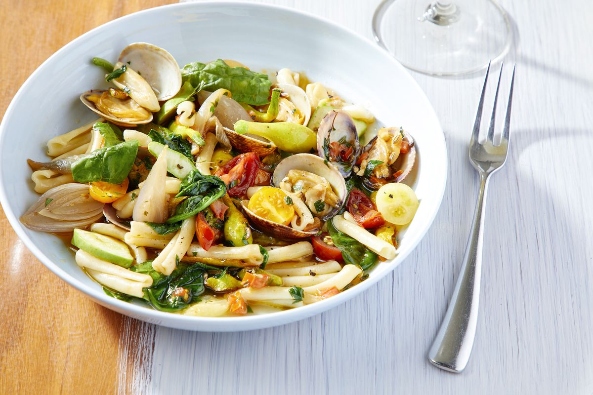 A plate of tubular pasta with garden veggies and clams.