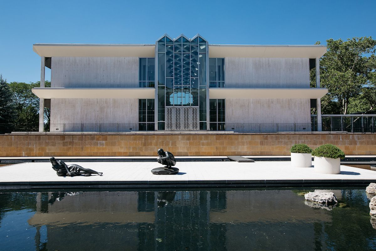 The exterior of the McGregor Memorial Conference Center. There is a large glass skylight over the entrance. In front of the building is a pool and various sculptures.
