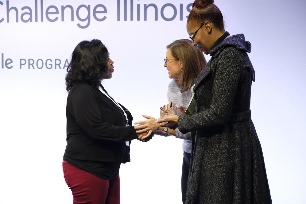 Team members of Chicago's True Star Foundation, a group teaching youth digital skills and entrepreneurship, shake hands with Google Site Lead Karen Sauder, accepting their award as one of 10 finalists snagging $75,000 in Google's Impact Challenge Illinois