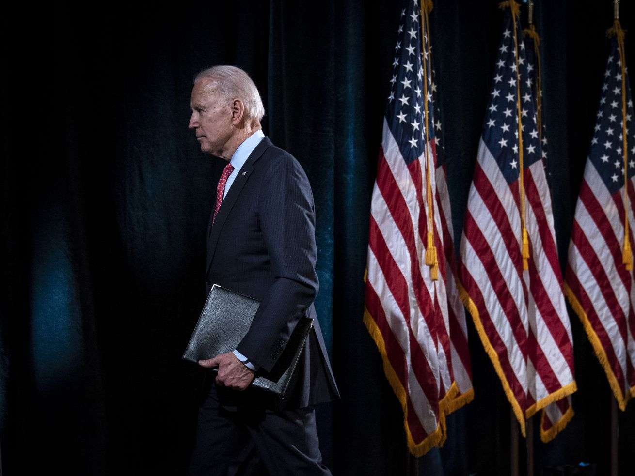 Biden clutches a leather binder as he walks past three US flags, while wearing a dark suit.