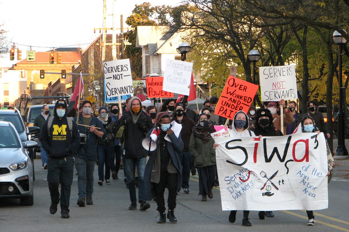 """A photo of masked protesters from SIWA3 marching through the streets of Ann Arbor. Some hold signs reading """"Servers, Not Servants."""""""