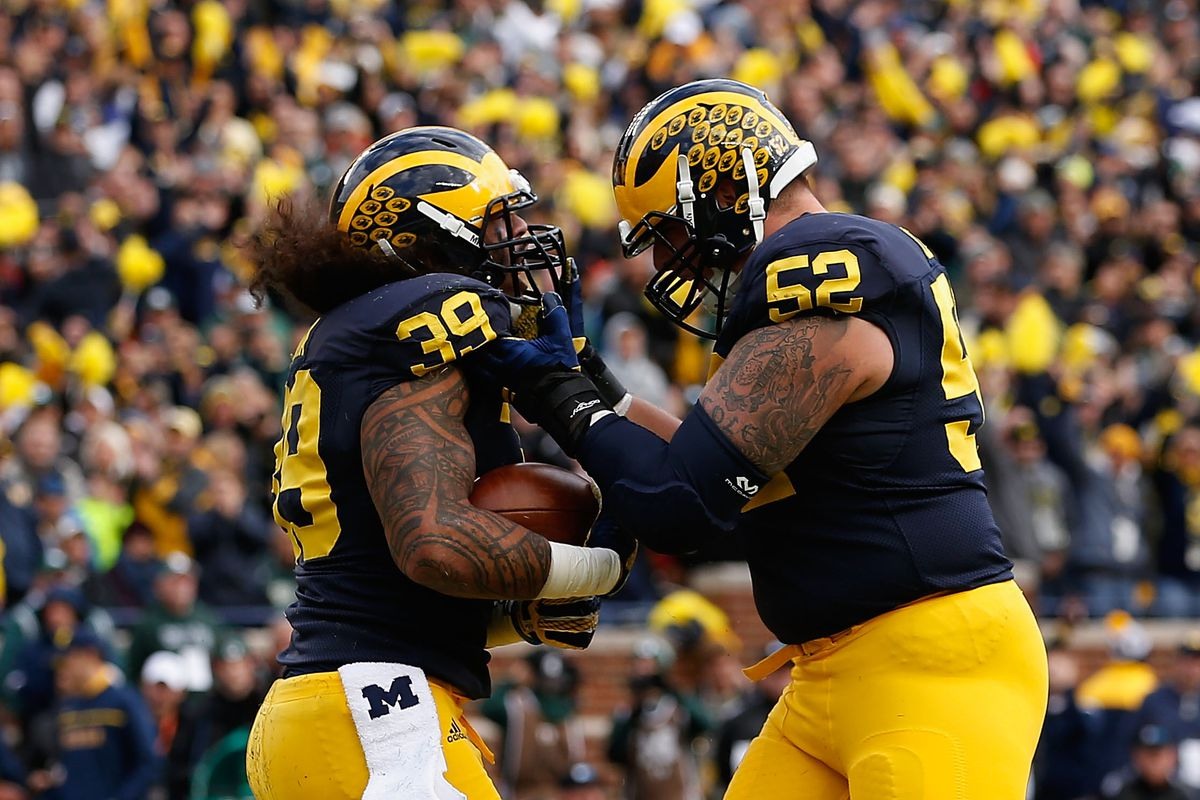 ANN ARBOR, MI:  Michigan Wolverines offensive lineman Mason Cole (52) celebrates with fullback Sione Houma (39) after a short-yardage touchdown score against the Michgian State Spartans at Michigan Stadium.