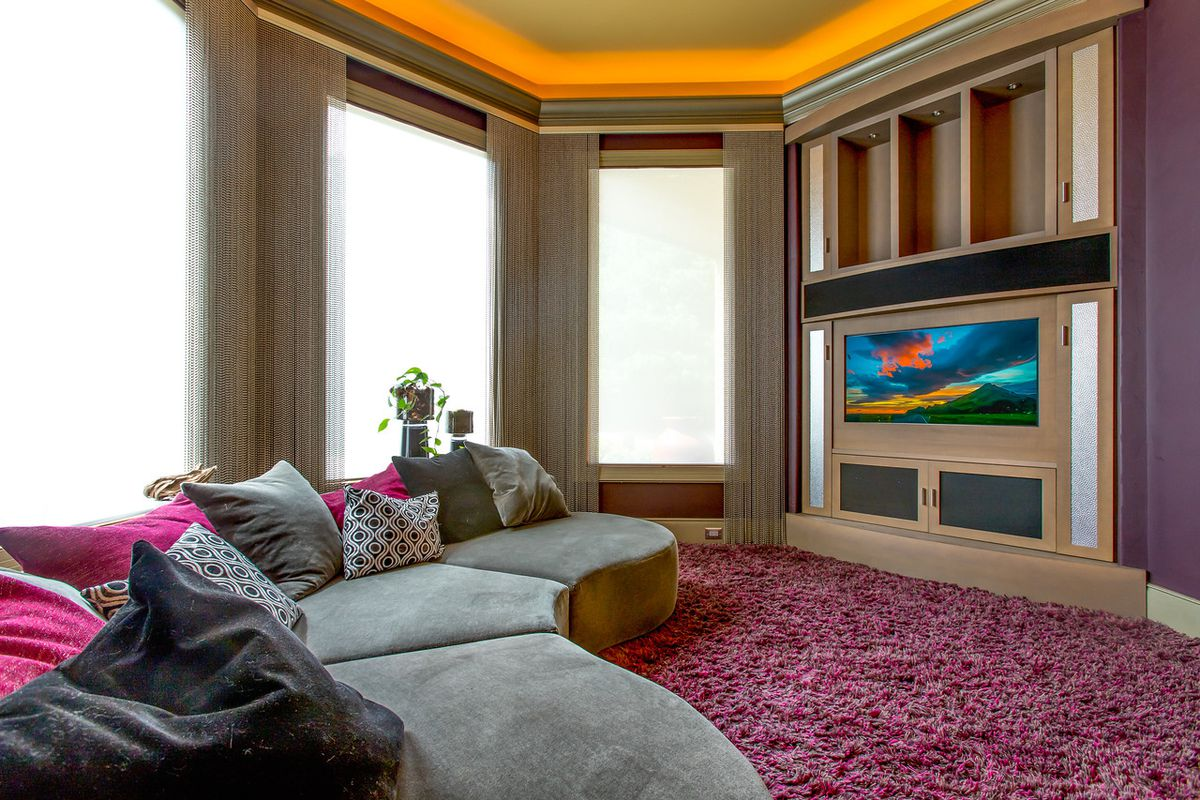 A big room with a purple rug and TV.