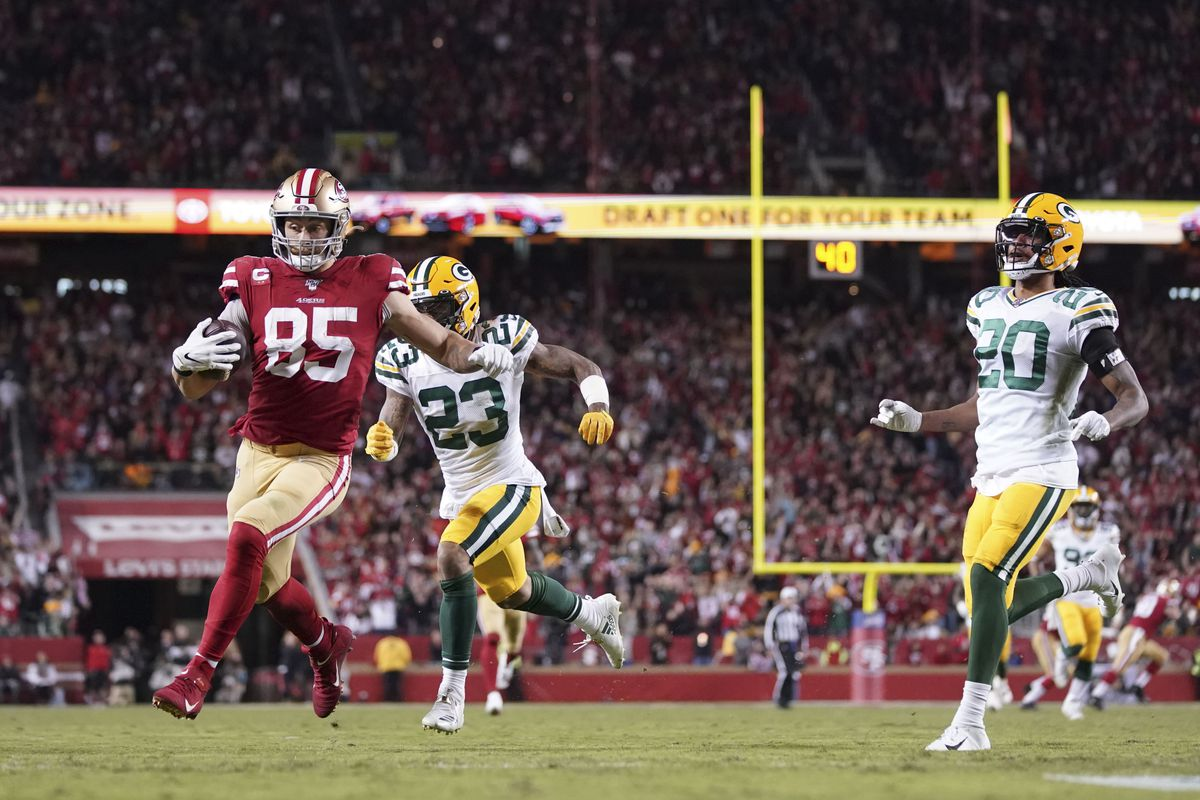 San Francisco 49ers tight end George Kittle scores a touchdown against Green Bay Packers cornerback Jaire Alexander and cornerback Kevin King during the third quarter at Levi's Stadium.