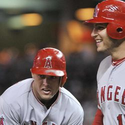 Los Angeles Angels' Chris Iannetta, right, smiles as Peter Bourjos comes out of his slide at the plate on Bourjos' three-run, inside-the-park home run off Minnesota Twins pitcher Carl Pavano in the fifth inning of a baseball game Wednesday, April 11, 2012, in Minneapolis.