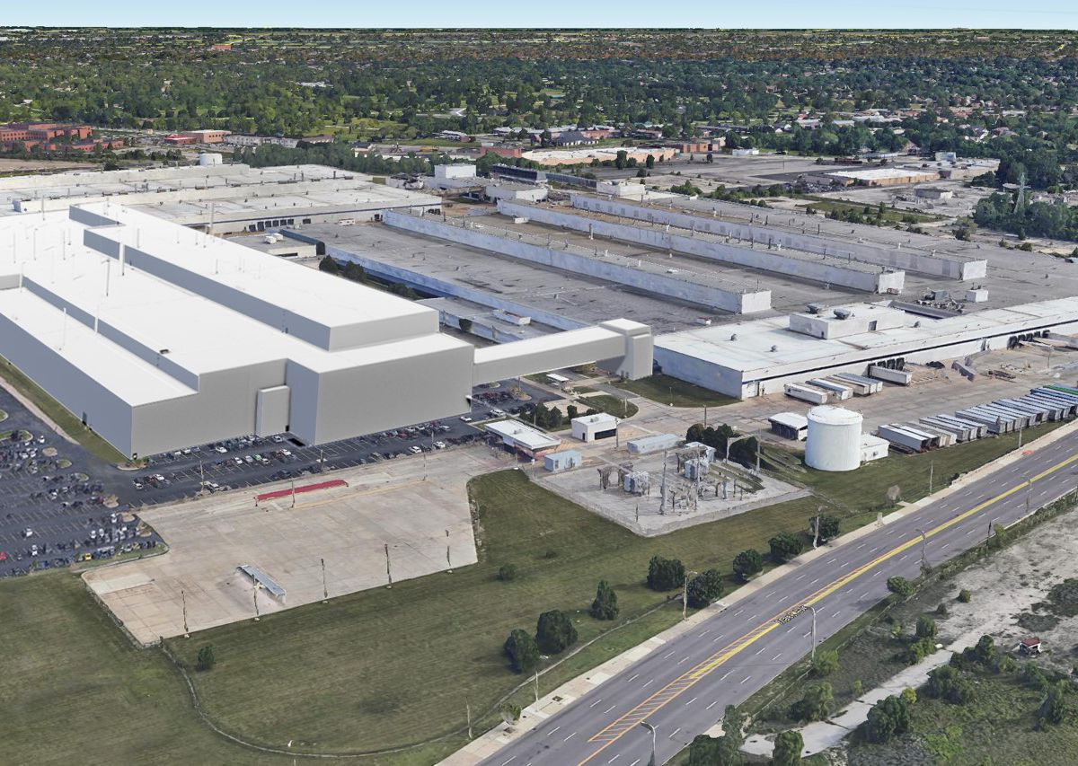An aerial view of a factory and surrounding buildings. The buildings are all very long and are surrounded by parking lots and grassy lawns.
