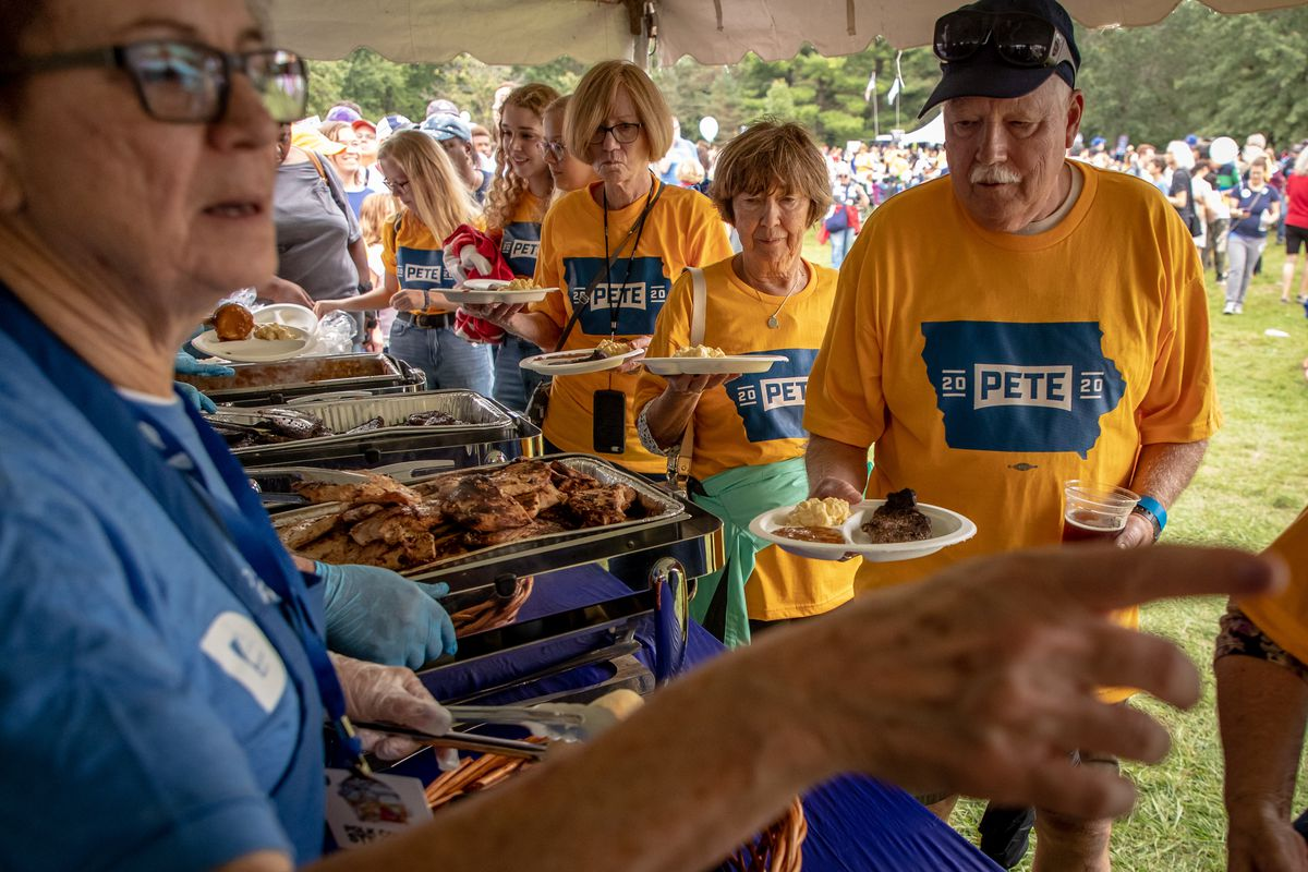 """People wearing """"Pete 2020"""" shirts stand in a buffet line."""