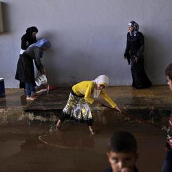 In this Wednesday, Sept. 5, 2012, photo, Syrians, who fled their homes due to fighting between the Syrian army and the Rebels, swipe the ground at the spot where they are taking refuge at the Bab Al-Salameh border crossing, in hopes of entering one of the refugee camps in Turkey, near the Syrian town of Azaz. The days are still hot across the fertile plains of northern Syria, but at night there is a hint of a chill an ominous harbinger of winter's approach and the deepening of the humanitarian crisis gripping a country wracked by civil war.
