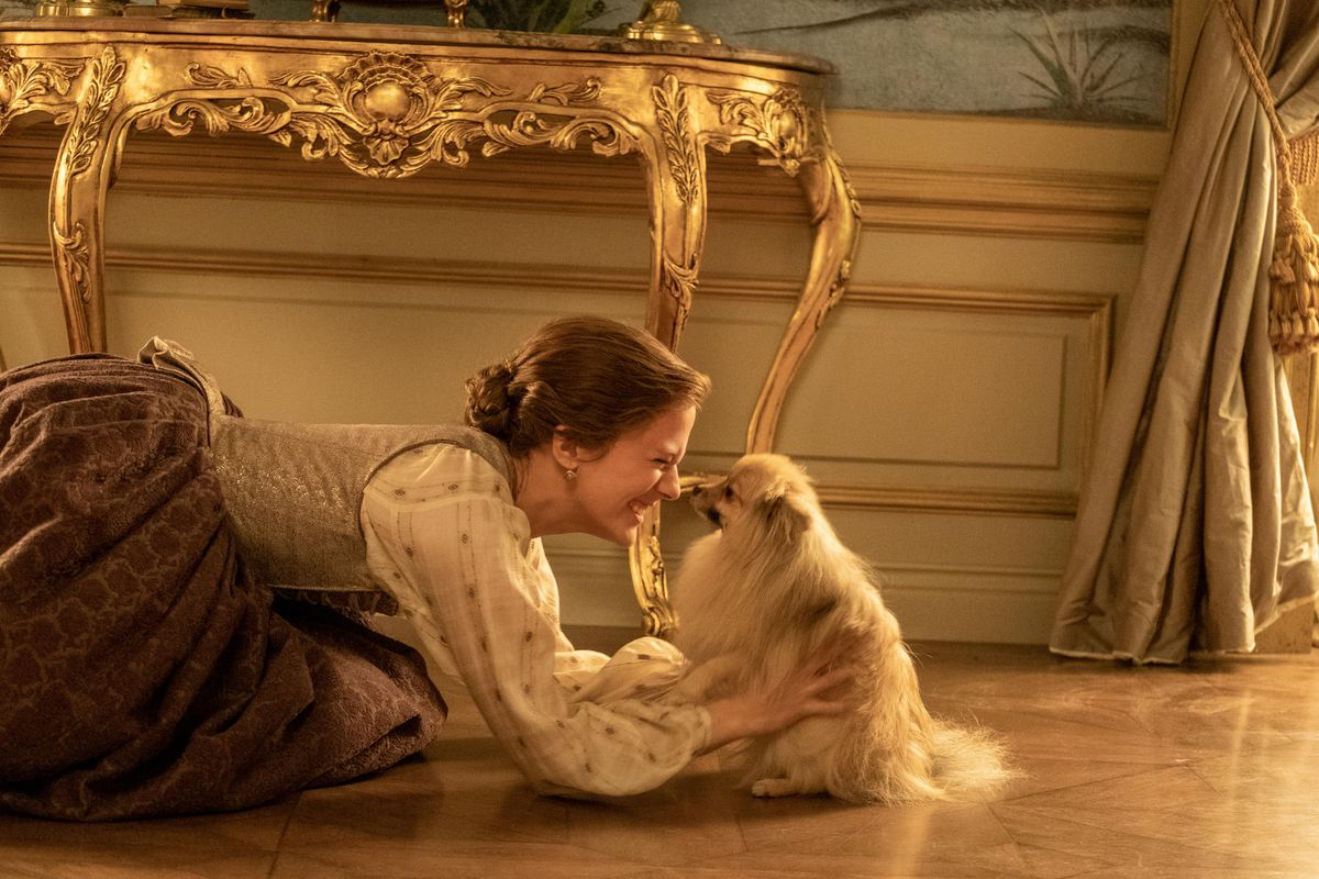 A woman on her knees in front of an elaborate gold-leafed table nuzzles a small fuzzy dog in Hulu's historical drama The Great.
