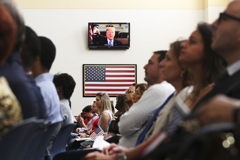 President Trump is seen on a television screen addressing new US citizens.