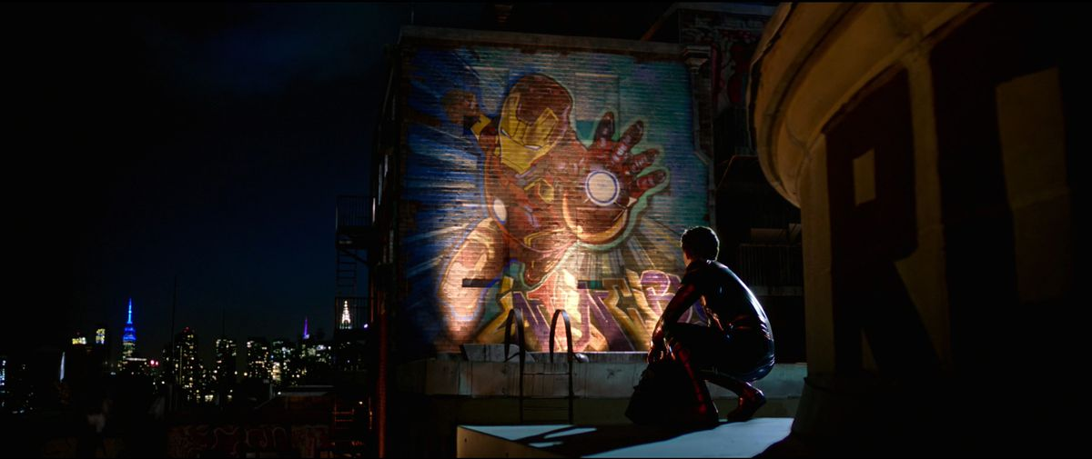 spider-man aka peter parker looks at a mural of iron man in far from home