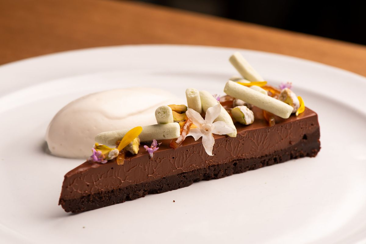 A thin slice of chocolate cremeux dessert with cream next to it on the plate.
