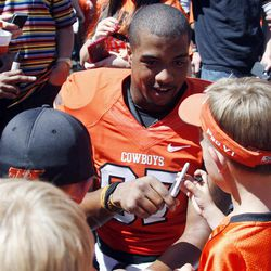 Oklahoma State wide receiver Tracy Moore signs autographs for young fans following a spring NCAA college football game in Stillwater, Okla., Saturday, April 21, 2012.