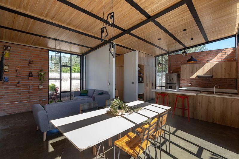 White dining table next to open plan kitchen.