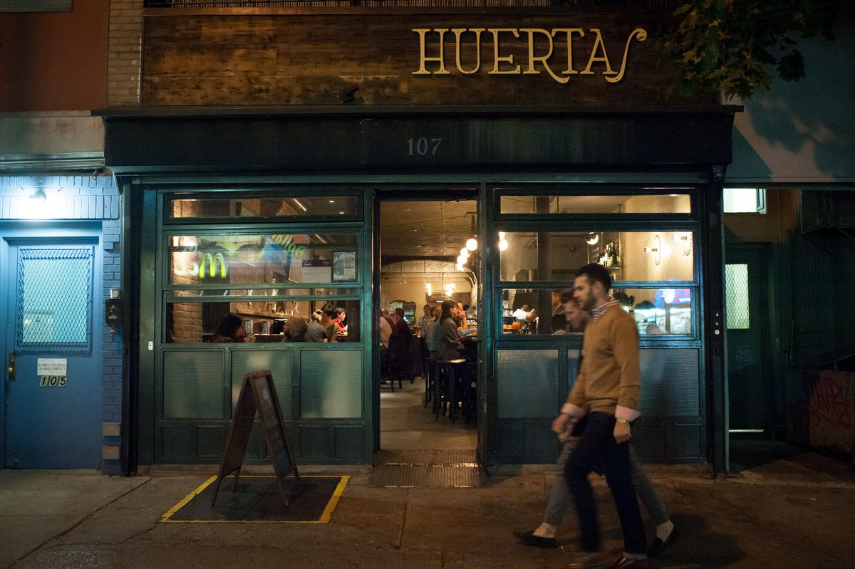 The Huertas restaurant storefront is filled with people, as two people walk by at night.