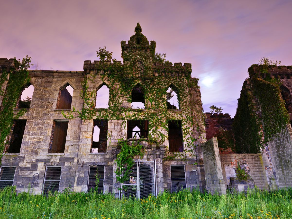 The exterior of the Renwick Smallpox Hospital. The building is abandoned. There are multiple windows and the facade is stone. There is moss growing on some parts of the facade. It is evening and the sky is purple.