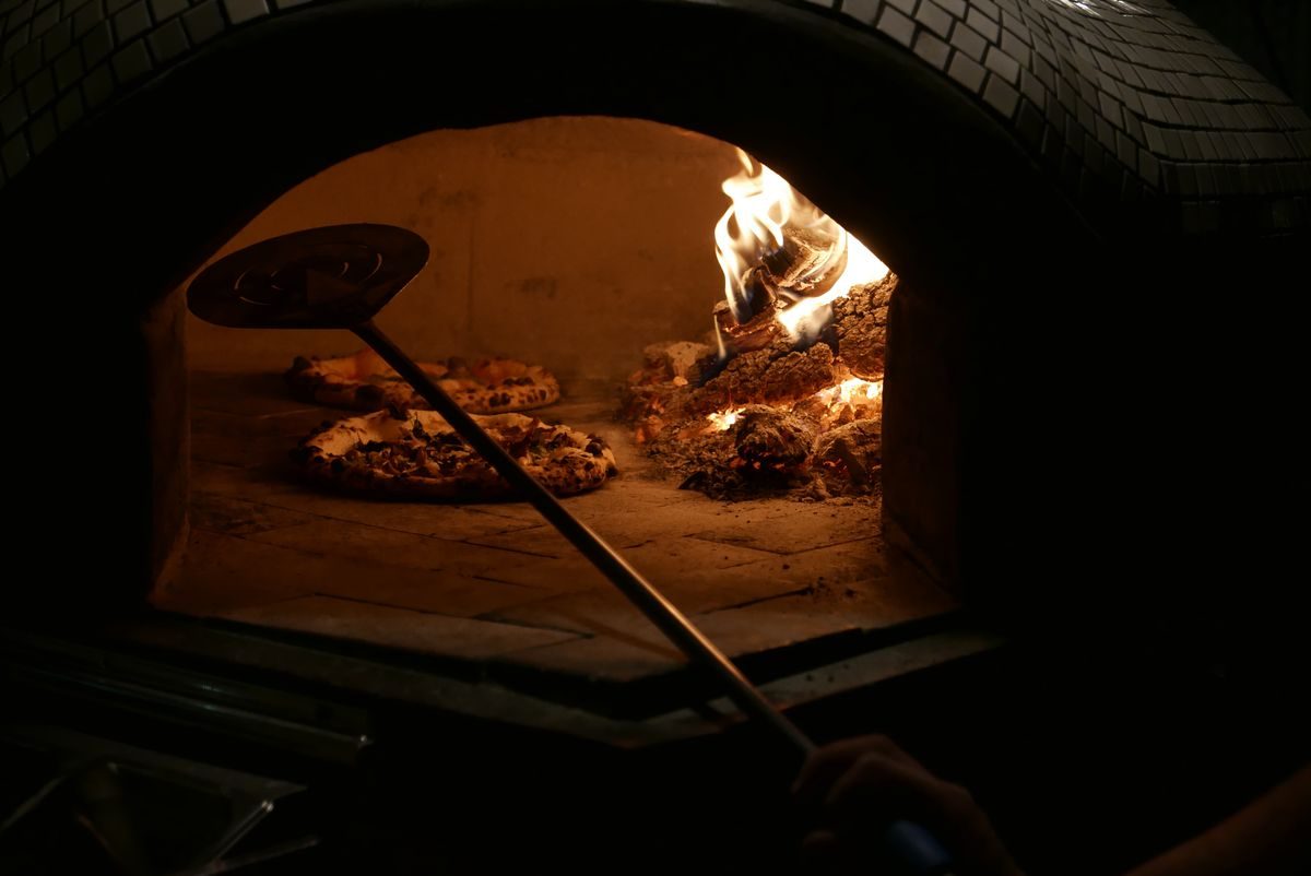 The inside of a wood-fired pizza oven containing two pizzas