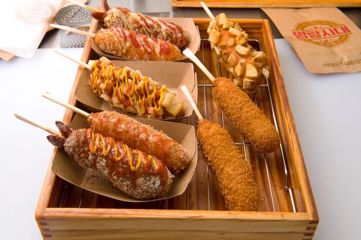 Eight Korean street style hot dogs, deep fried and served on a stick.